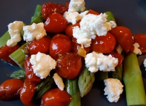 A photo of asparagus with balsamic tomatoes and goat cheese.
